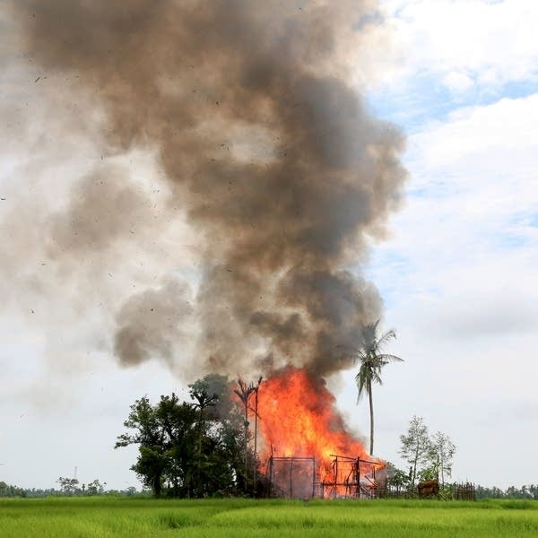 A house in Rakhine state is consumed by flames, as journalists look on.