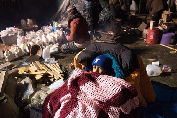 Ajay Kyle, 6, huddles under blankets near her dad.