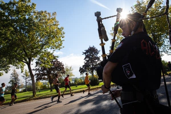 The sun shines over bagpiper as runners pass on a road.