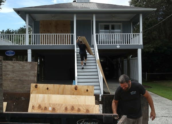 Clint McBride cuts plywood to be put over a home's window.