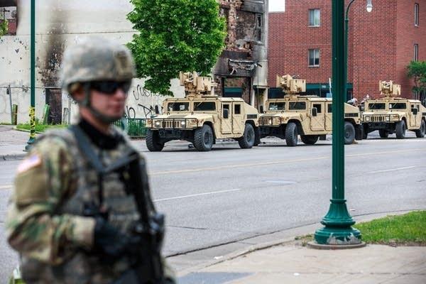 Minnesota National Guard soldiers patrol a street.