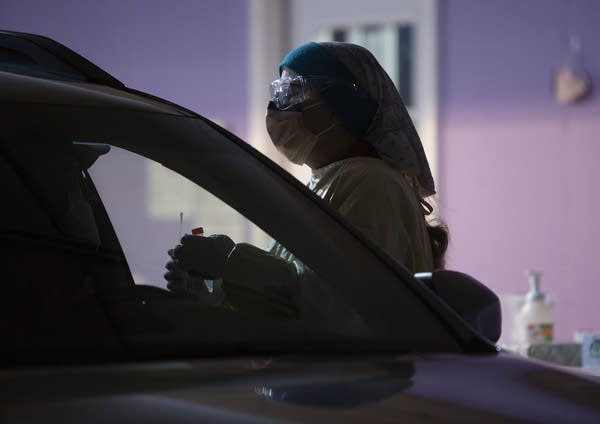 A person wearing PPE holds a nasal swab as she approaches a car.