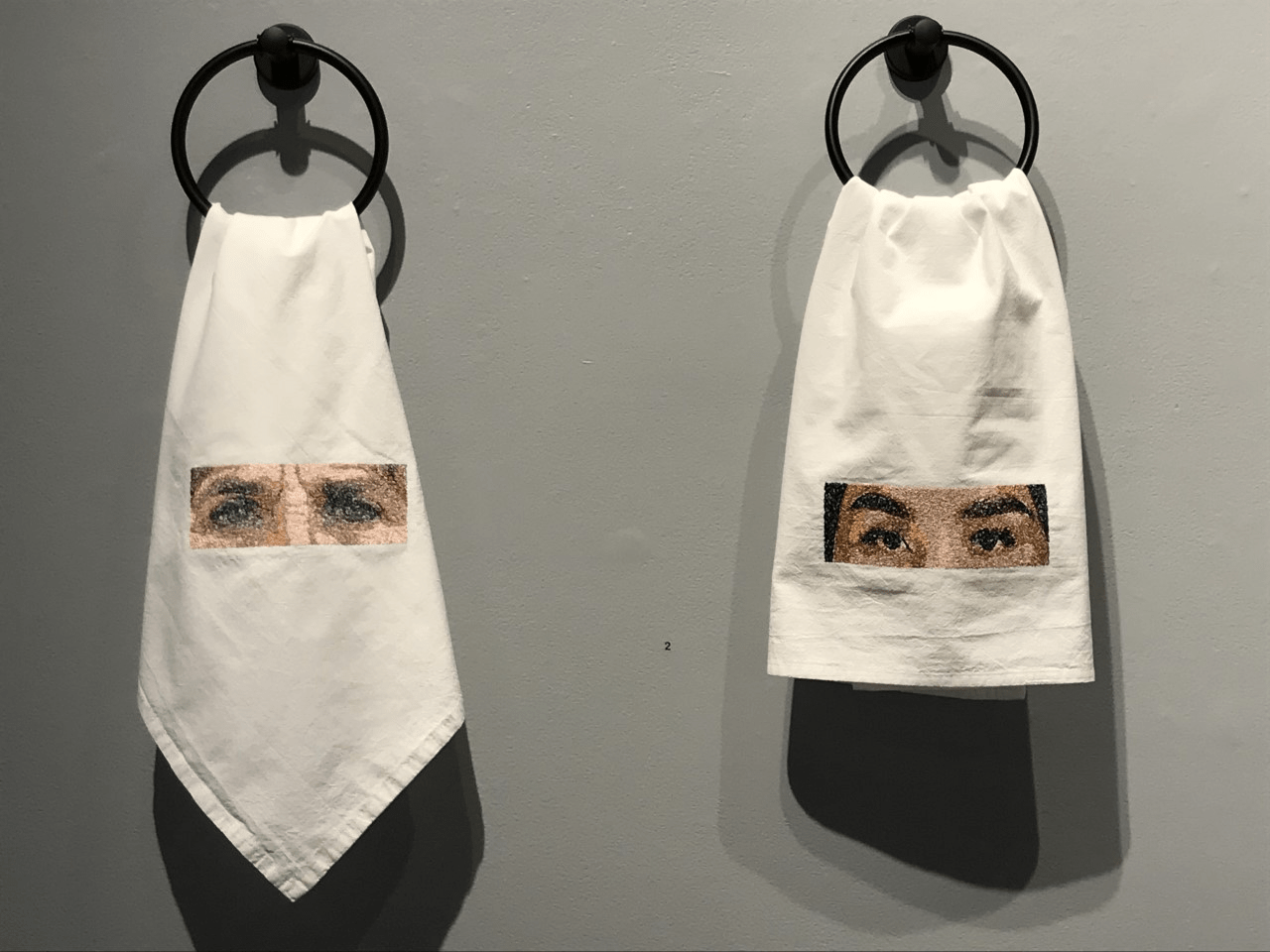 An art exhibit of two cloths with eyes on the cloths.