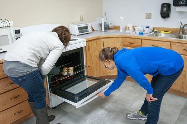 Two people open an oven door.