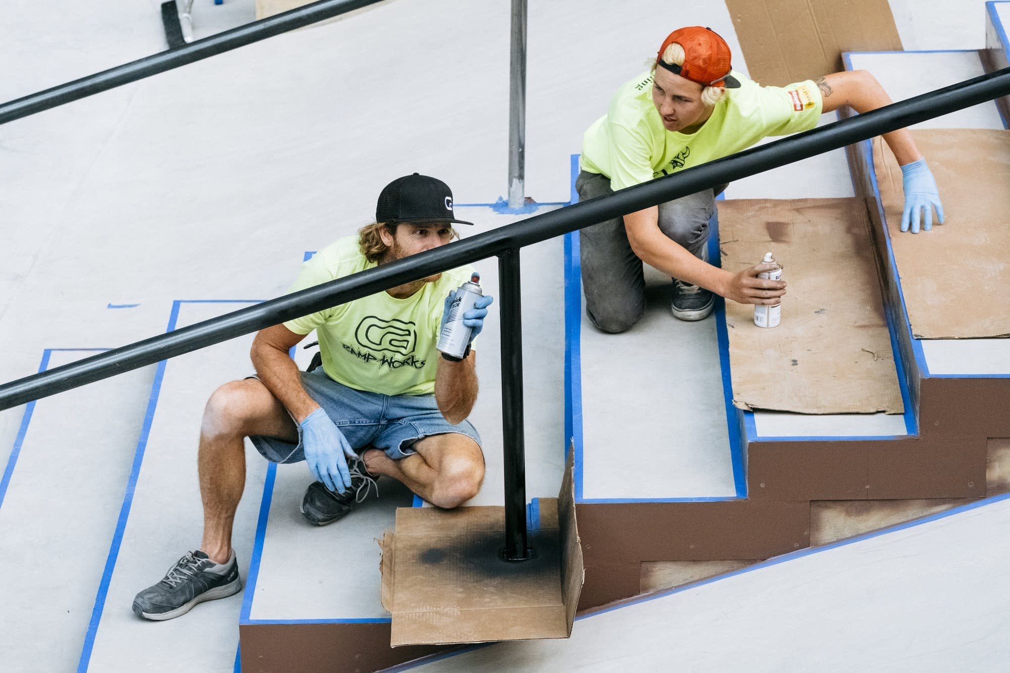 Workers spray paint a rail.