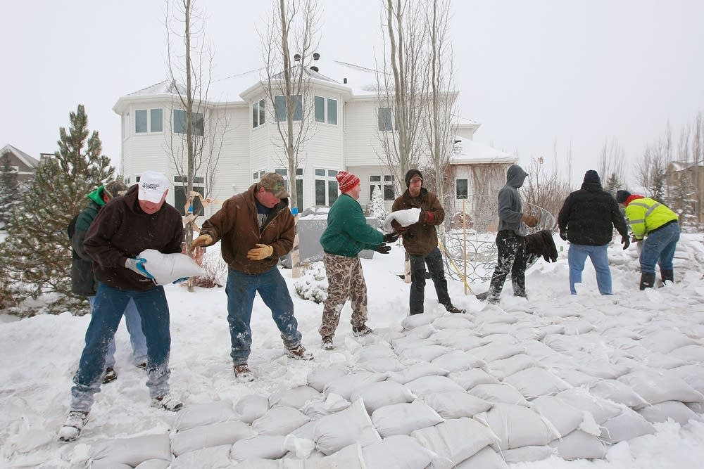 Volunteers build a sandbag levee