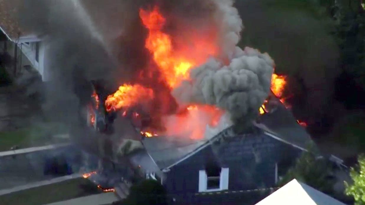 Flames consume the roof of a home in Lawrence, Mass.