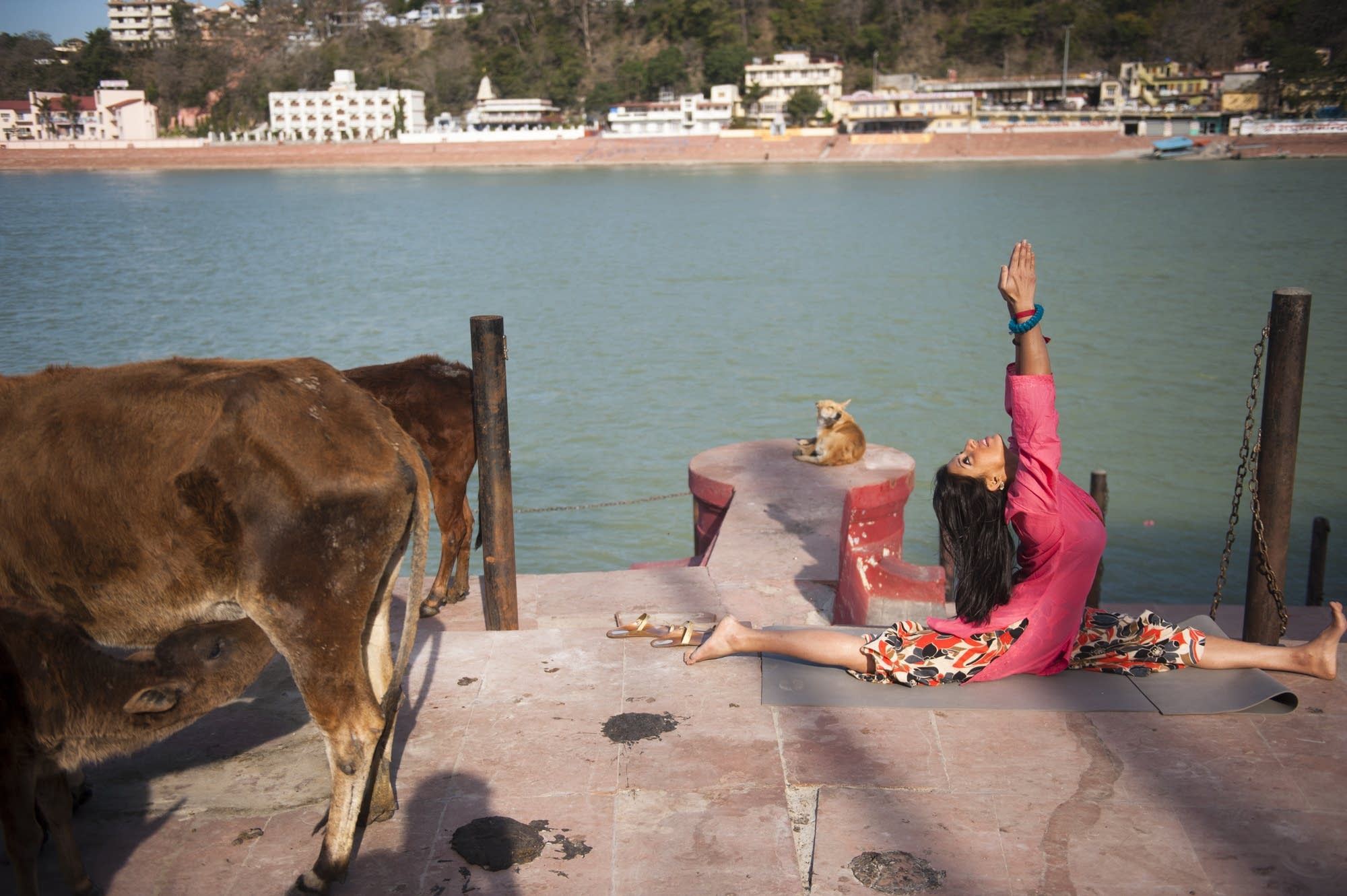 Woman practices yoga, Ganges River.