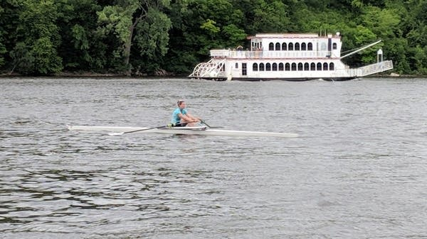 A boat from the Mpls. Rowing Club rowed upriver past the Mississippi Queen.