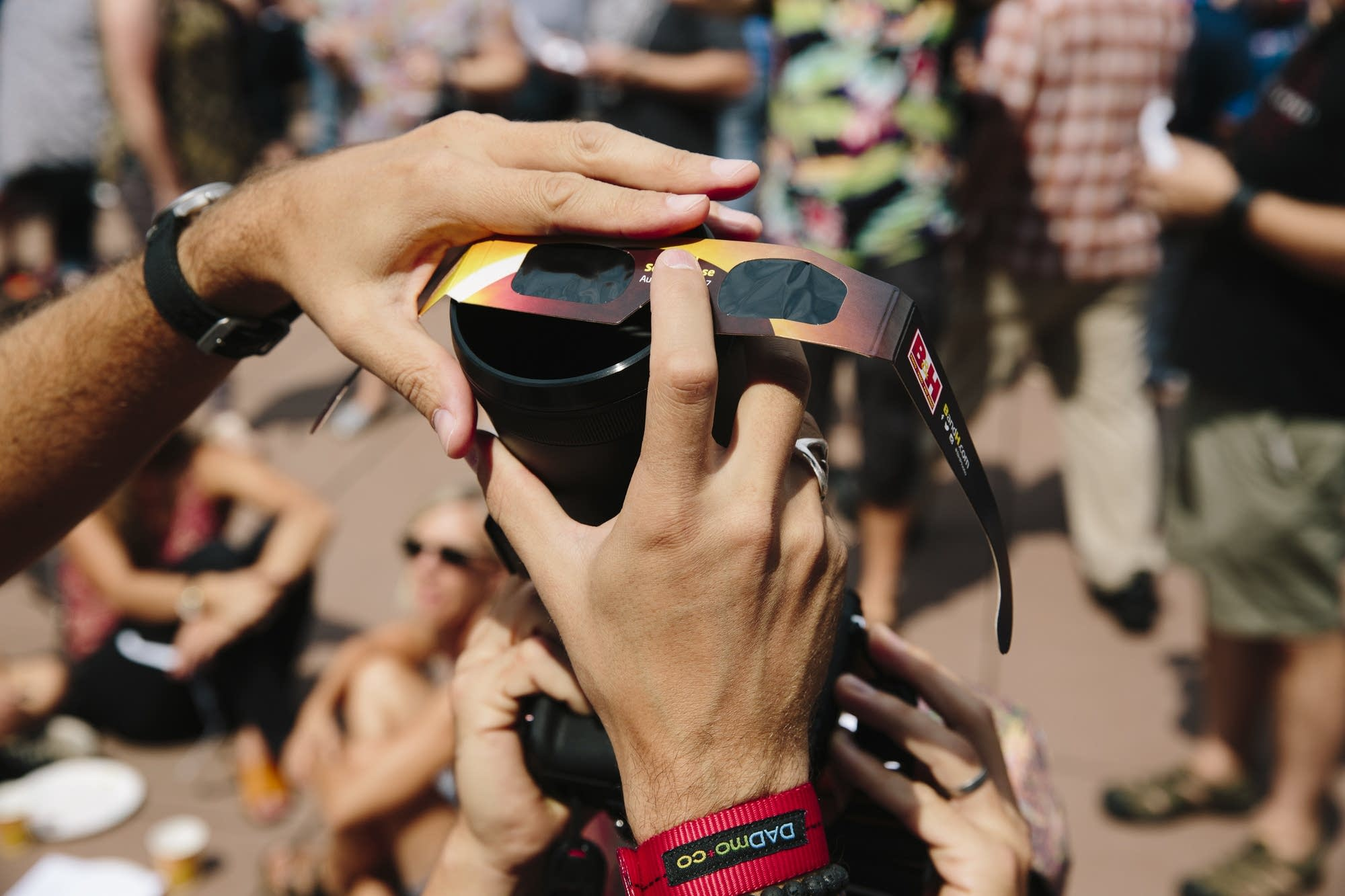 People hold eclipse glasses in front of a camera.