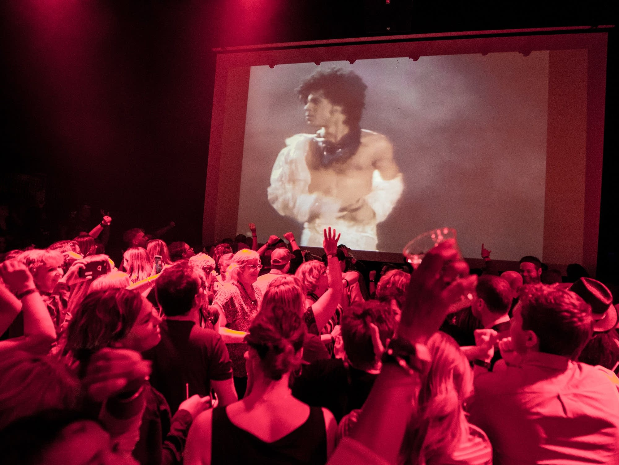 Prince fans dance while images of the musician appear on a screen.