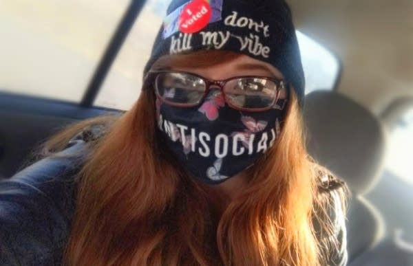 A person wearing a face mask, sunglasses and a hat with an I voted sticker