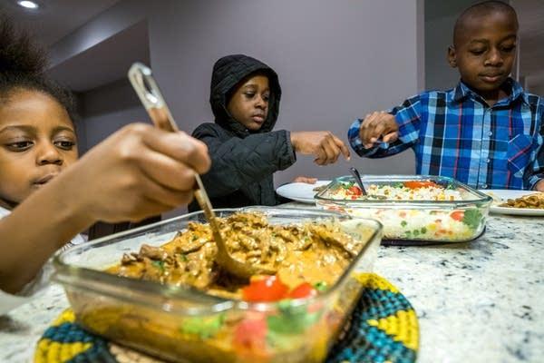 The Mphiri children serve themselves dinner.