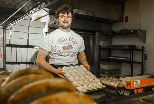 A man holds a pan of unbaked croissants.