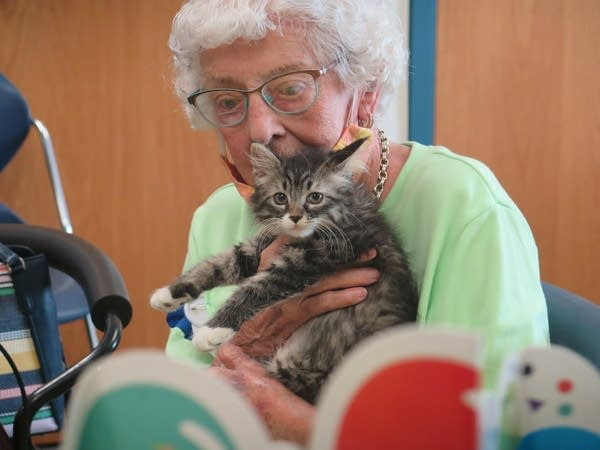 A old lady holds a kitten.