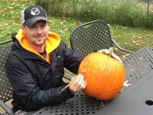 Ryan Lisson poses with a pumpkin as he completes a surface carving on it.