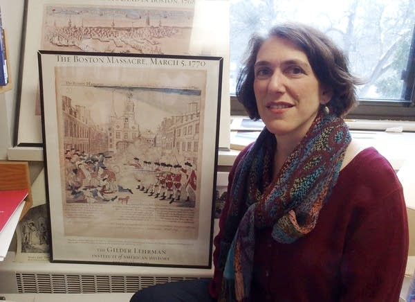 A woman sits beside a framed replica of an engraving.