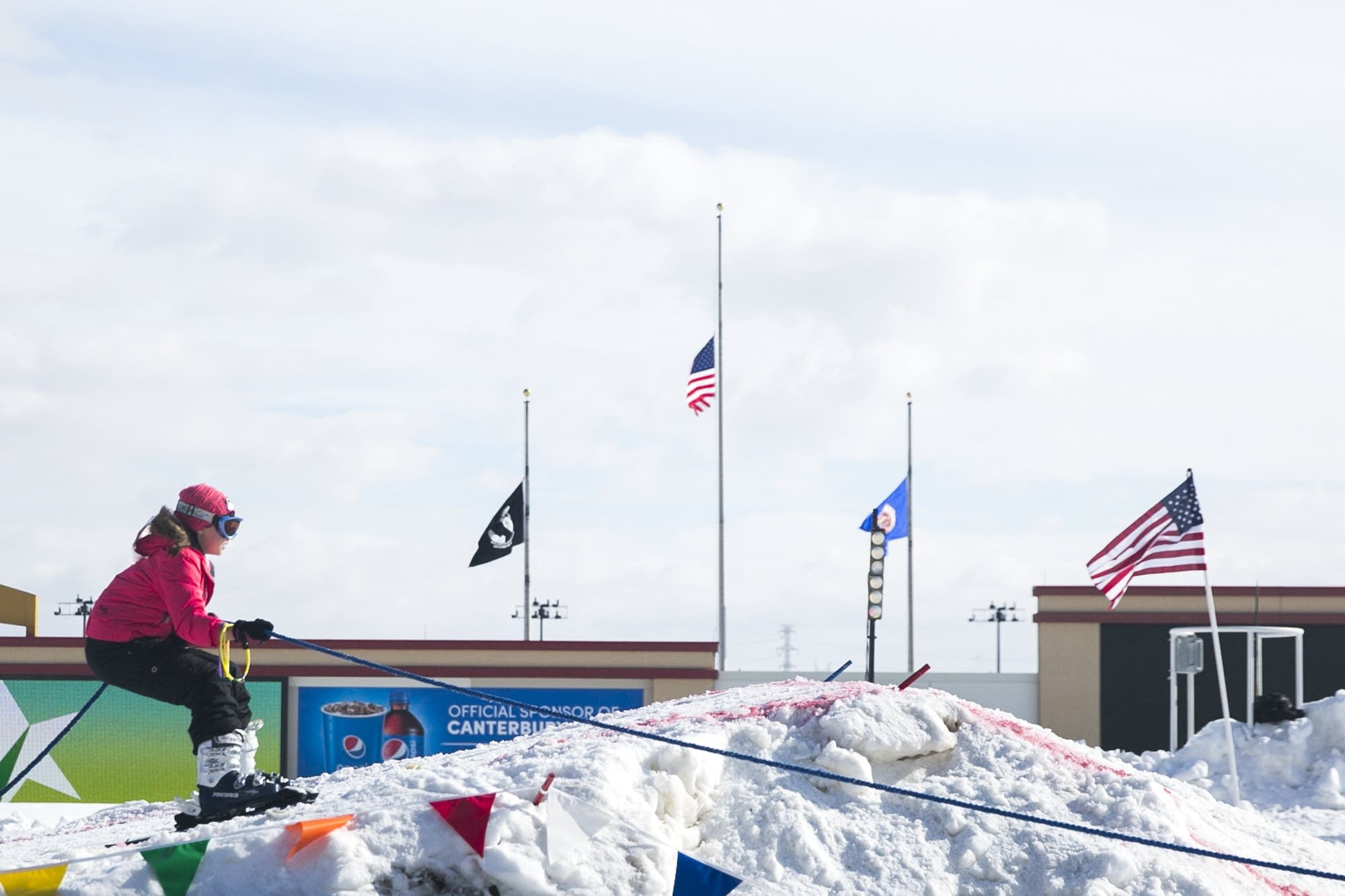 Flags at Canterbury Park fly at half staff as a racer gets ready to jump.