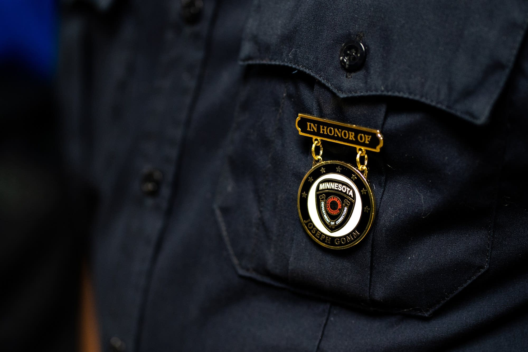 A corrections officer wears a pin commemorating Joseph Gomm.