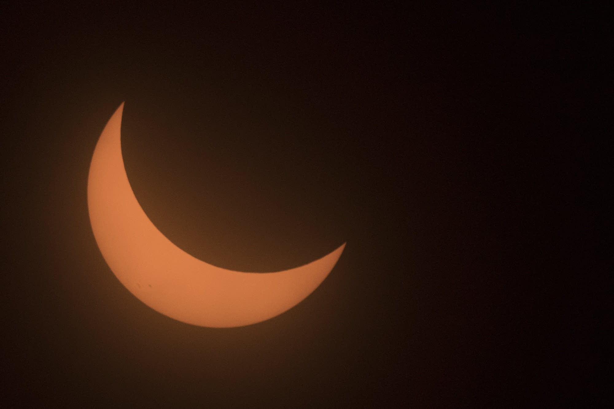 The sun, looking like a crescent moon, moves near totality.