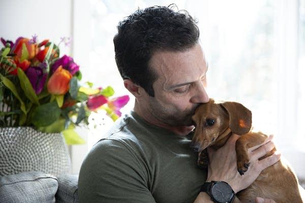 A man kisses the top of a dachshund's head.