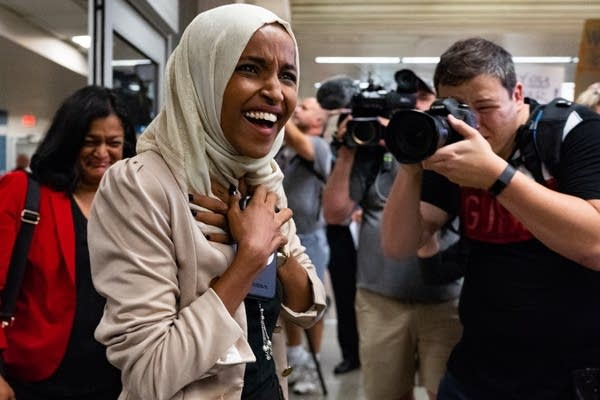 Ilhan Omar, wearing beige, smiles and holds her hands over her chest.