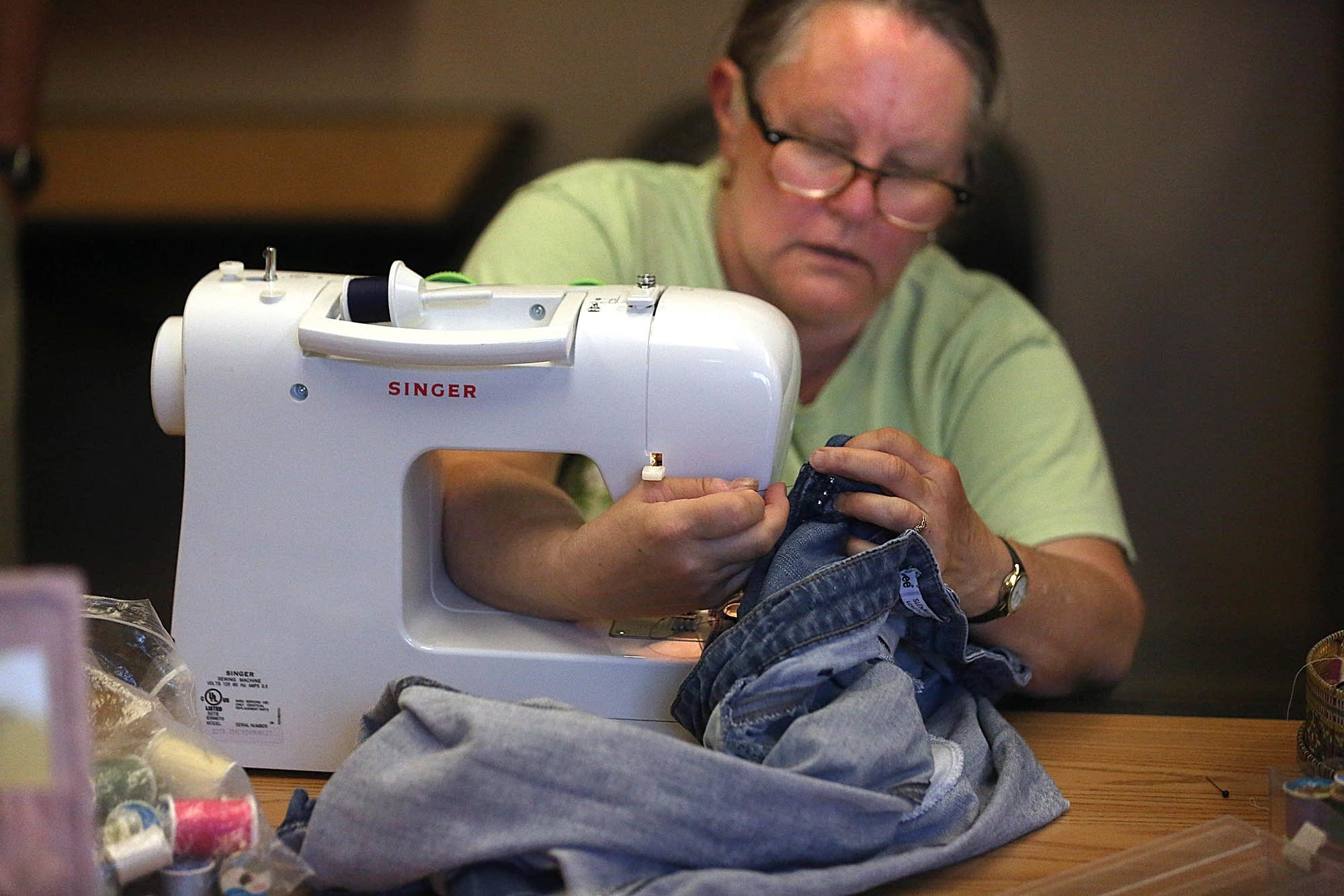 Cathy Jensen, Hudson, mends a pair of jeans.