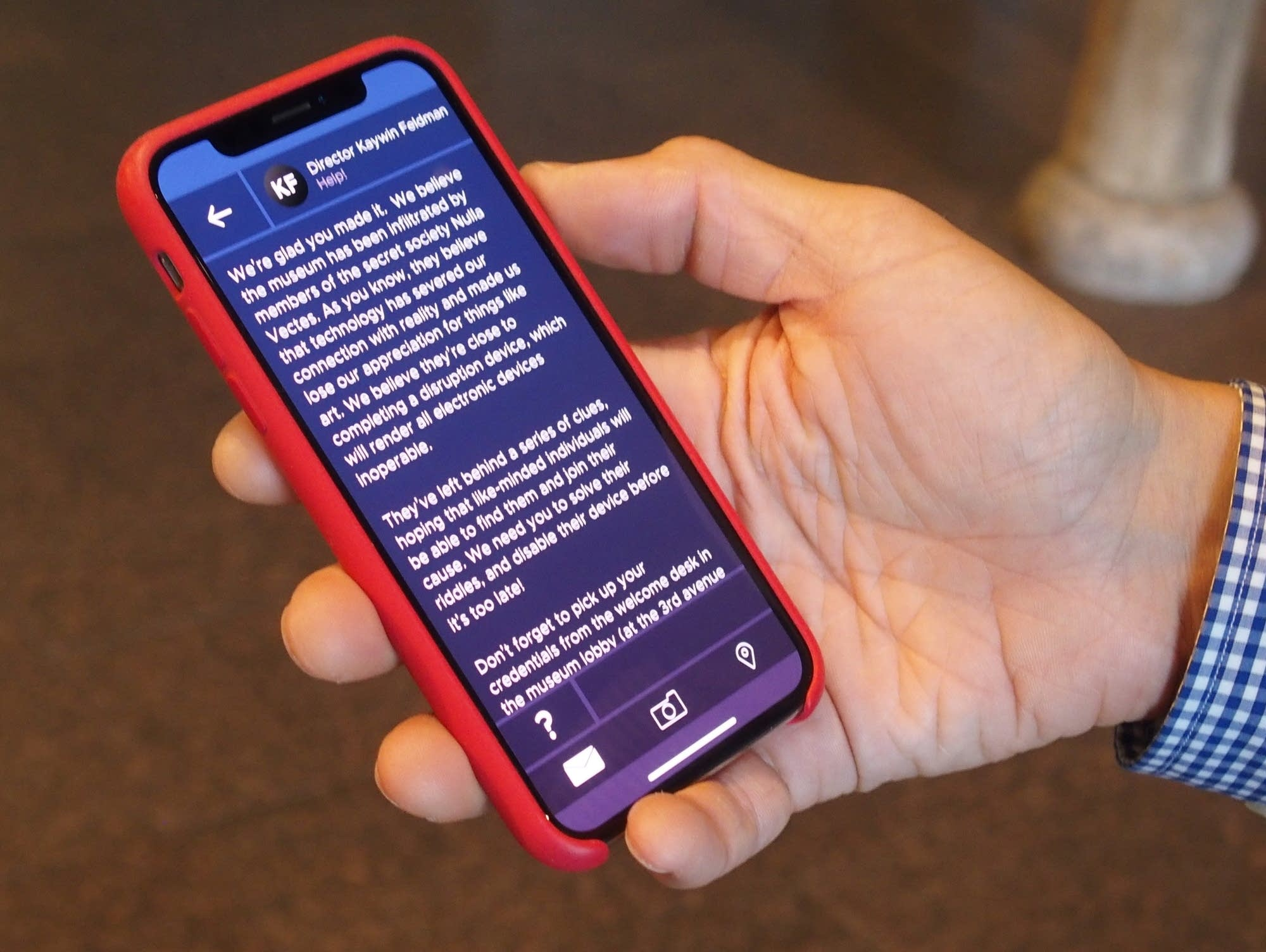 Colin McFadden holds a smartphone with the first message in the game.