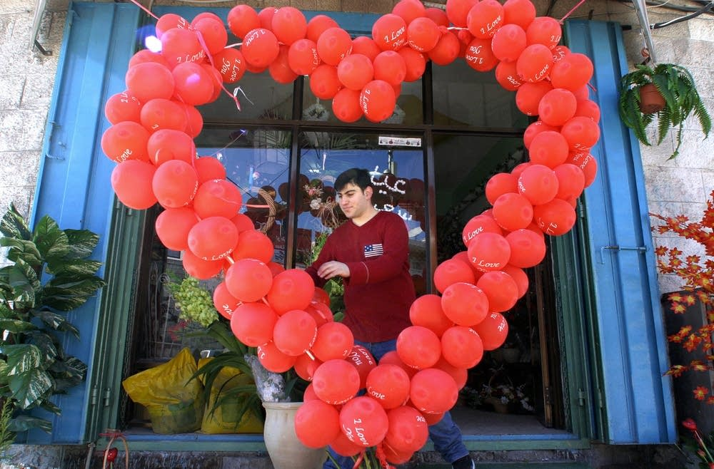 A man places a heart made of ballons outside a shop (Jamal Aruri/AFP/Getty Images)