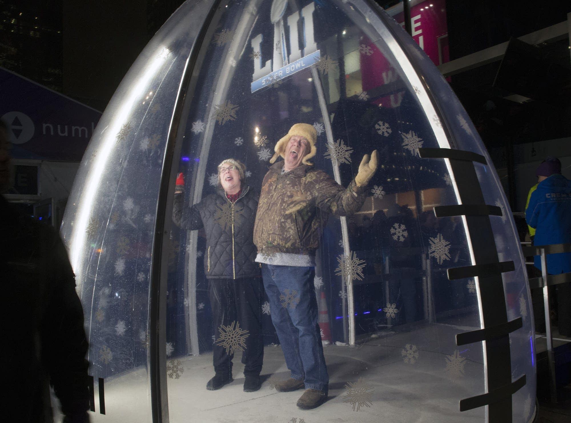 Becky and Chuck Human hammed it up inside of a plexiglass football.