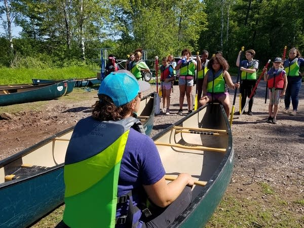 A group of girls listen as a woman talks in a canoe