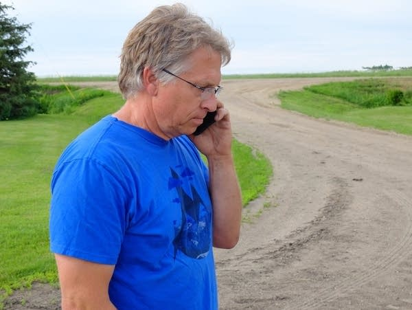 Mark Askegaard makes a phone call at his farm near Comstock, Minn.