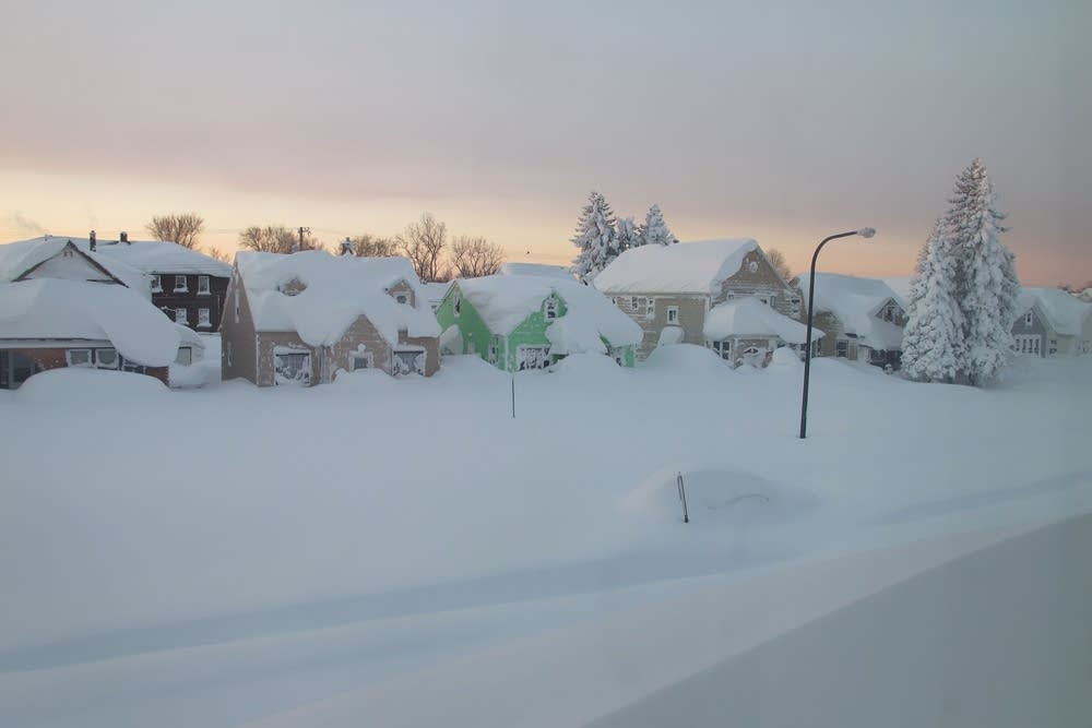 Snow covers a street at daybreak.
