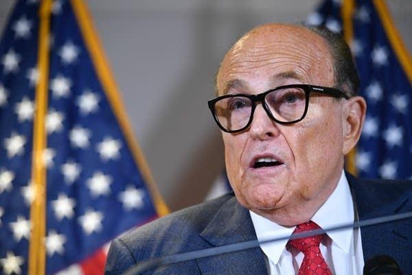 A man wearing glasses speaks.