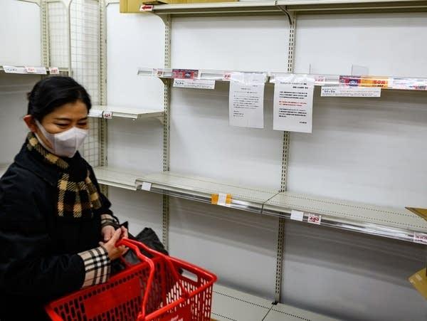 A woman wearing a face mask walks past empty supermarket shelves