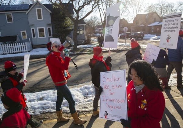 A group of people wearing red hold signs as they picket.