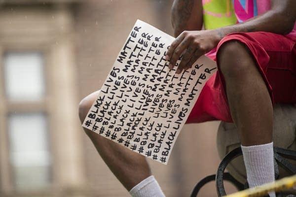 A man holds a Black Lives Matter sign.