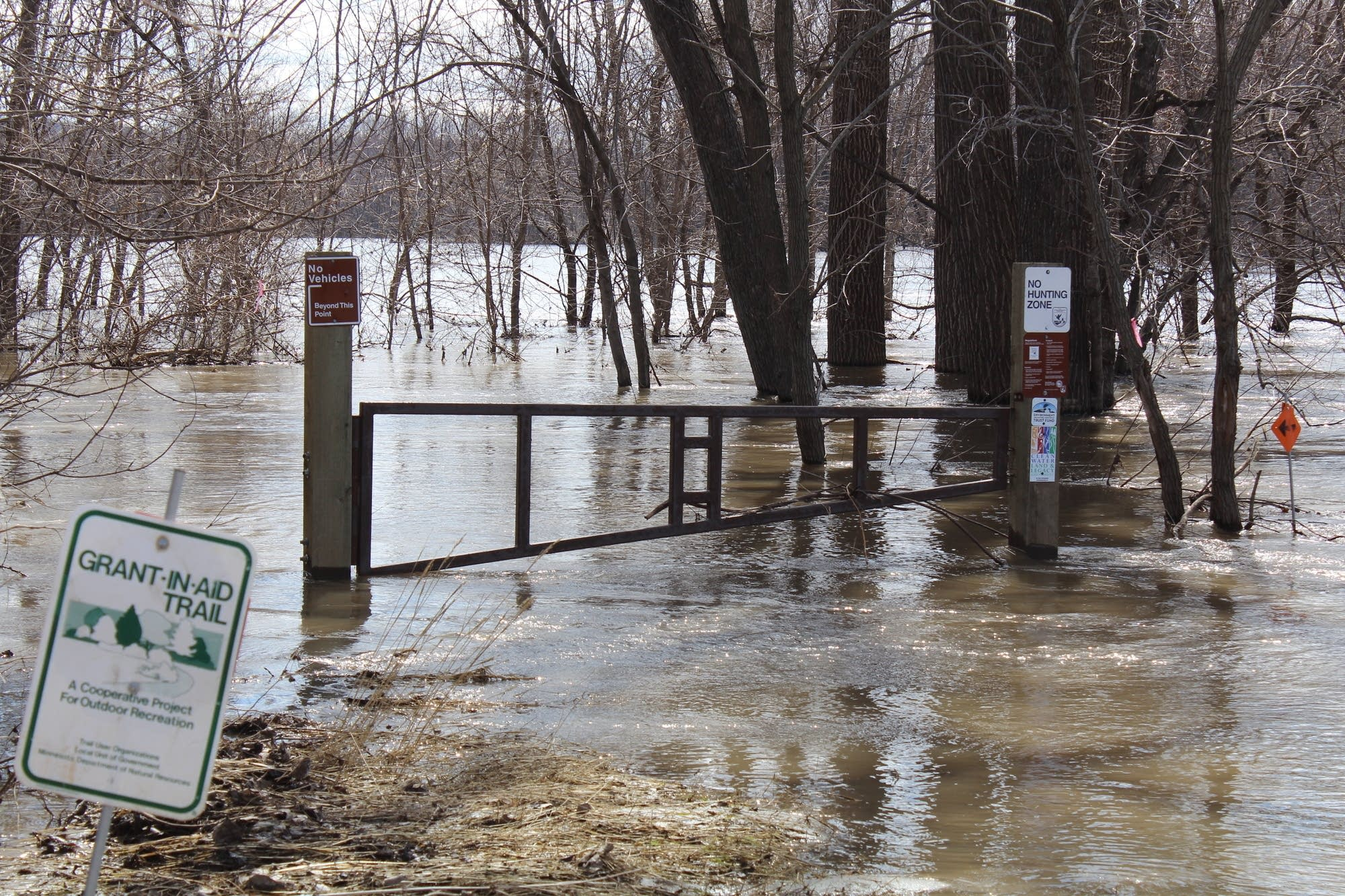 Floodwaters overtake a trail on the edge of Henderson, Minn.