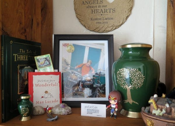 A green urn with a gold tree, books, framed photo and toys on a shelf.