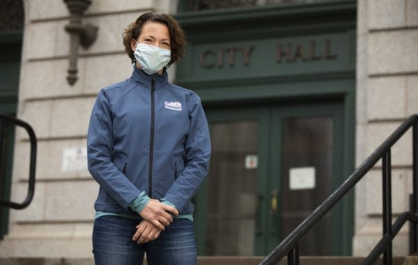 Person standing outside wearing a blue face mask.
