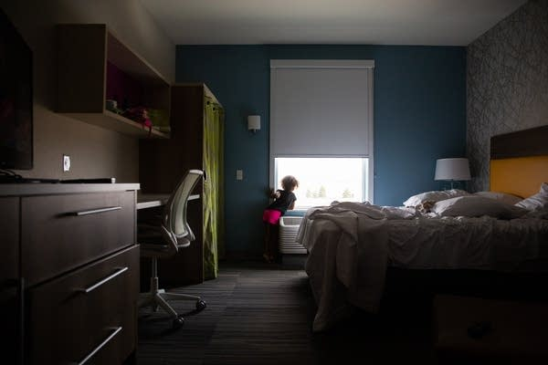 A young girl looks out the window of a hotel.