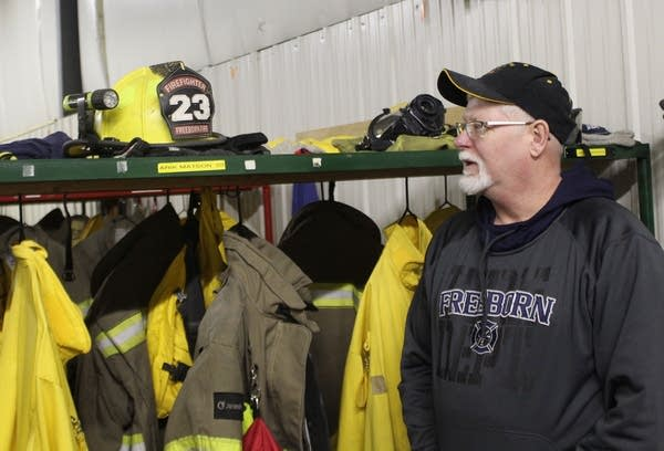 A man standing beside lockers with firefighter helmets and jackets.