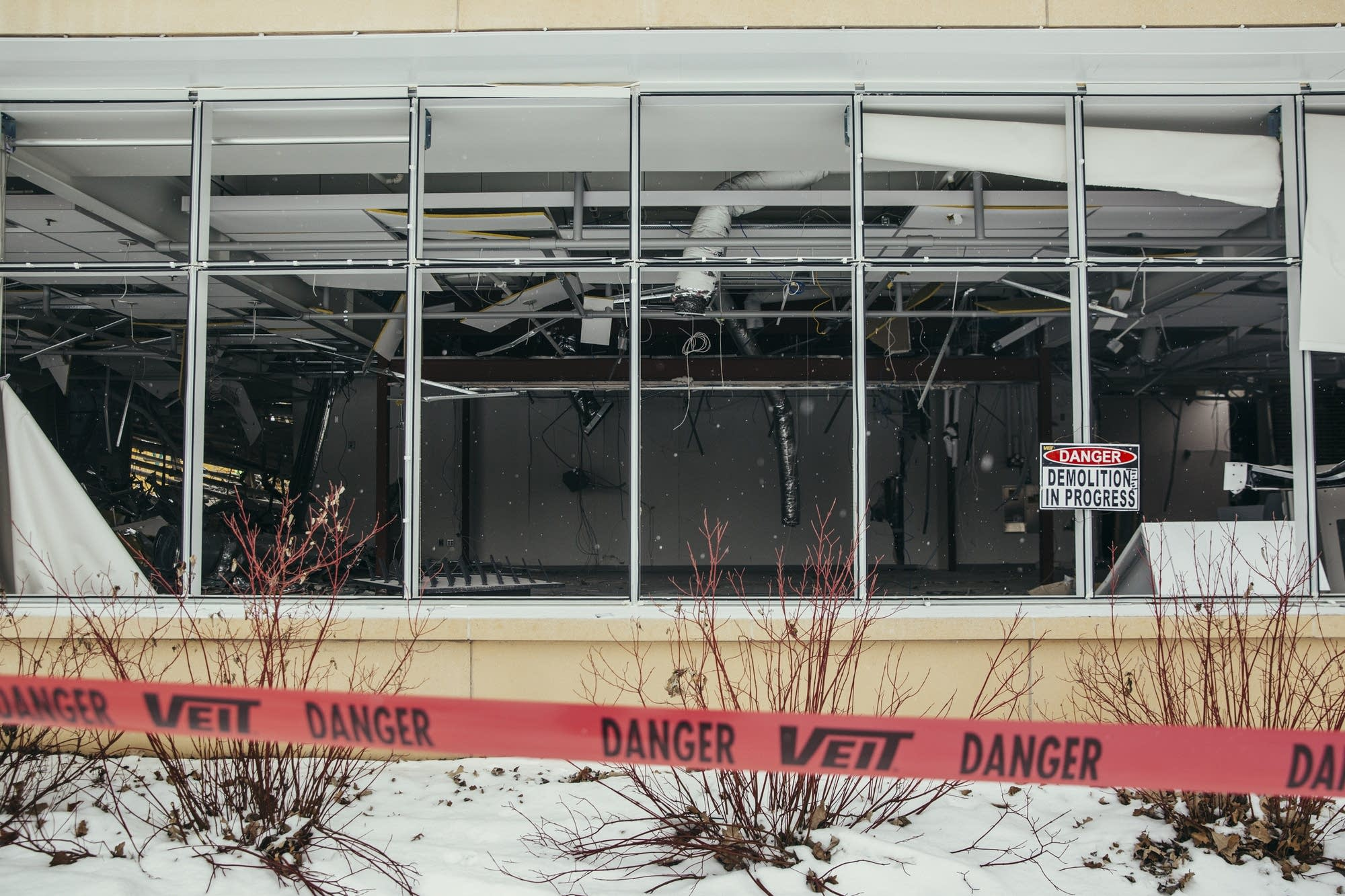 Snow falls in front of the destroyed Minnehaha Academy insides.