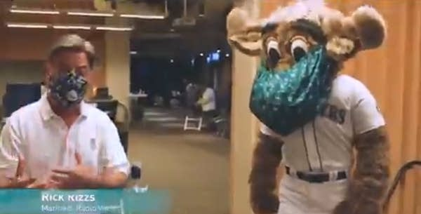 Video still of announcer Rick Rizzs standing next to a masked Mariner Moose
