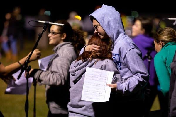 "Two students hug after singing at a ""Gathering of Hope"" even."