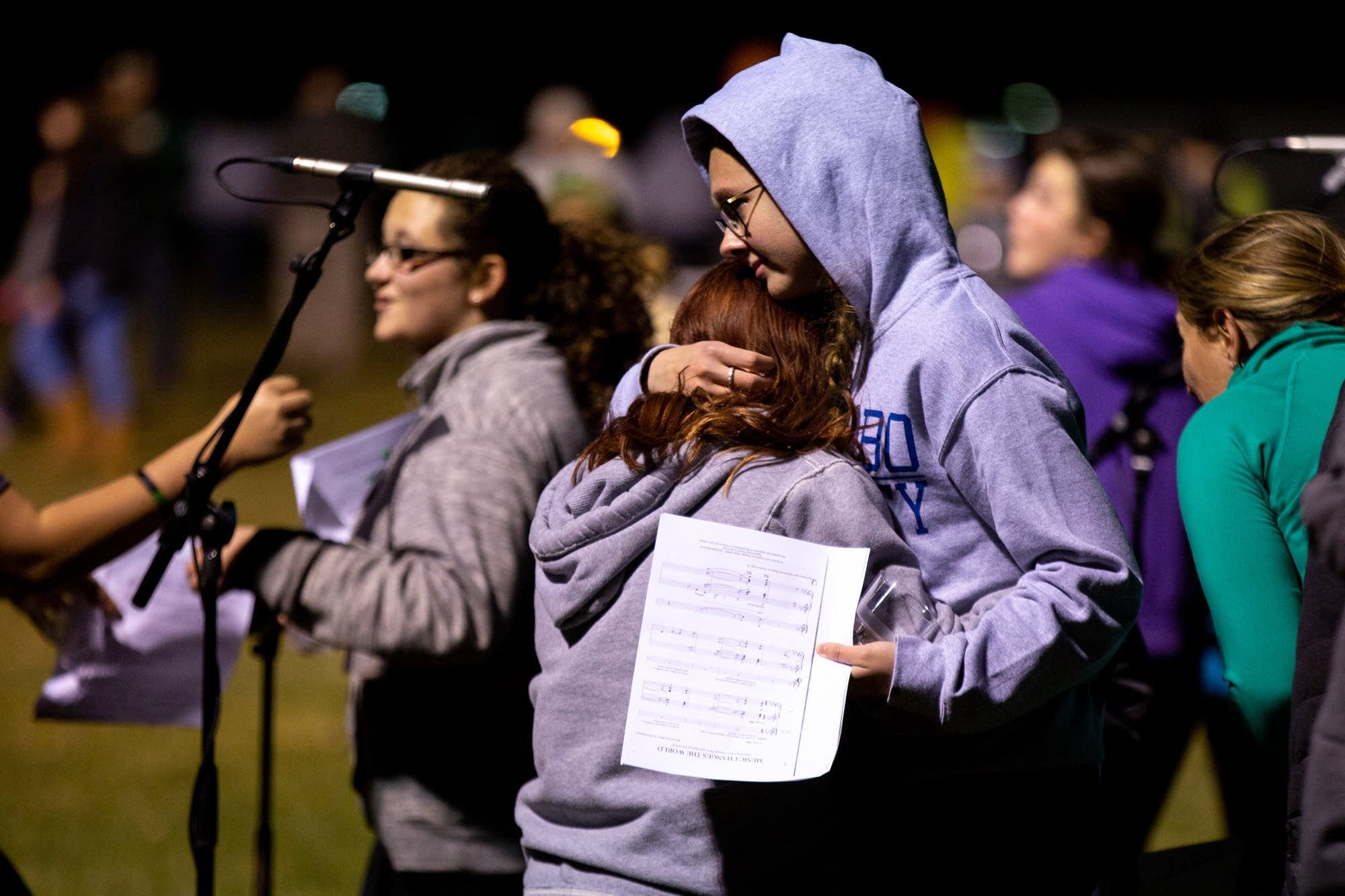 Two students hug after singing at a