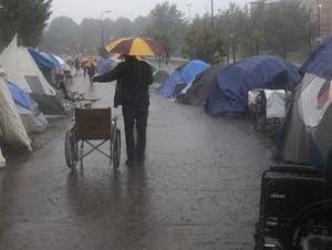 Heavy rain pours onto the homeless encampment.