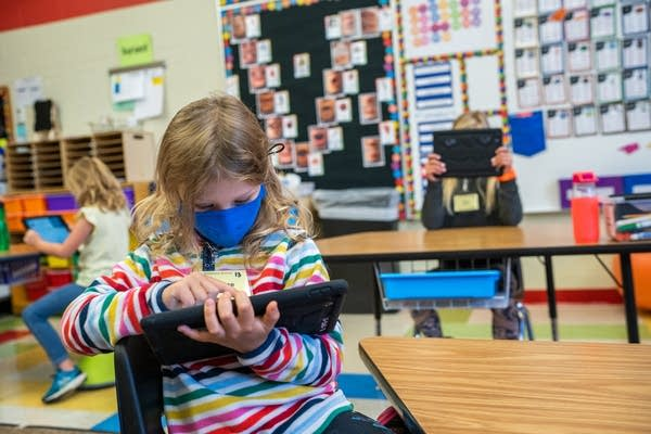 Students in masks play on tablets.