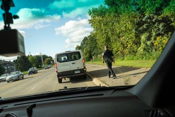 A police officer walks toward a white van under a blue sky.