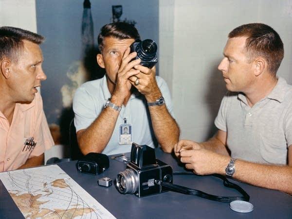 Astronaut Walter Schirra checks out his spacecraft's camera equipment